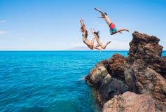 Falaise d'amis sautant dans l'océan Photos stock