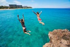Falaise d'amis sautant dans l'océan Images libres de droits
