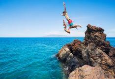Falaise d'amis sautant dans l'océan Photographie stock