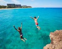 Falaise d'amis sautant dans l'océan Image stock