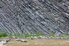 Falaise rocheuse d'une rivière de montagne Image stock