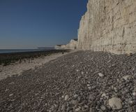 Falaises blanches, cailloux gris et cieux bleus - sept soeurs, East Sussex, Angleterre photos stock