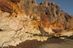 Falaises colorées sur la plage Photo stock