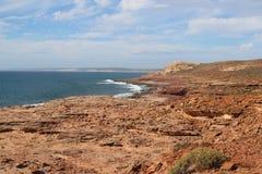 falaises de Rouge-pierre contre l'eau bleue et le ciel images stock