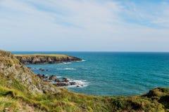 Falaises herbeuses vertes et mer d'Irlande bleue Images libres de droits