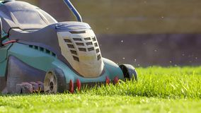 Falciatrice da giardino che taglia erba verde in cortile Immagini Stock