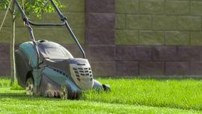 Falciatrice da giardino che taglia erba verde in cortile Fotografia Stock