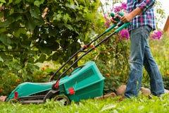Falciatrice da giardino di Mow Grass With del giardiniere in giardino fotografia stock