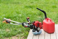 Falciatrice da giardino e bidone per la benzina con benzina sui precedenti di erba verde immagini stock