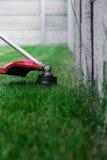 Falciatrice da giardino manuale sui precedenti di erba verde Fotografie Stock Libere da Diritti