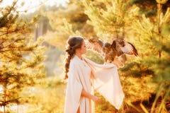 Falco con le ali spante che si siedono sul braccio di bella ragazza fotografia stock