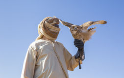 Falconer with a desert tawny Owl in a desert. Near Dubai Royalty Free Stock Image