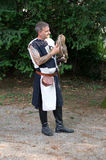 Falconer. Trezzo Folk and Fantasy 2014 Dressed in a medieval tunic, a falconer is holding a owl on his arm getting ready for the falconry display that took place royalty free stock image