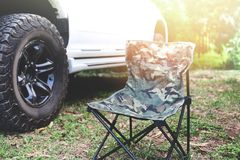 Falcowania krzesło na campingu Z z drogowym pickup i światła słonecznego tłem - Pykniczny krzesło fotografia royalty free