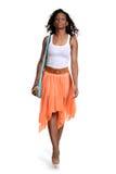 Falda anaranjada que lleva que camina de la mujer negra Foto de archivo