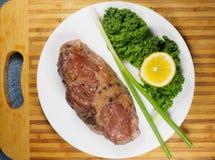 Falda de carne de vaca cocida en una placa con col rizada y la cebolla verde fotos de archivo