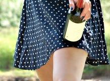 Falda en puntos con las piernas y la botella de vino imagen de archivo