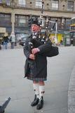 Falda escocesa que desgasta del montañés escocés que toca las gaitas Foto de archivo libre de regalías