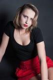 Falda roja y blusa negra en estudio Imagen de archivo