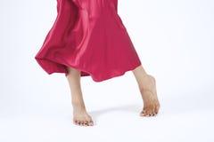 Falda y pies móviles rojos Fotografía de archivo