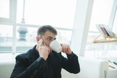 Fale pelo telefone em um café para um copo de um café Um homem em um terno senta-se em um restaurante moderno à moda e bebe-se o  Fotos de Stock Royalty Free