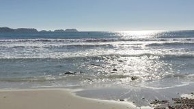 Fale rozbijają na piaskowatej plaży zbiory