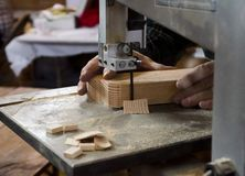 Falegname che per mezzo della sega a nastro sul pezzo di legno Immagine Stock