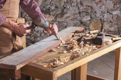 Falegname che per mezzo dello scalpello per lisciare giù legno fotografia stock