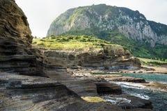 Falezy dosięga w oceanie przy Yongmeori plażą, Ro, Jeju wyspa, Południowy Korea Obrazy Stock