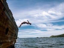 Falezy doskakiwanie: Młody facet w skrótach skacze w seawater od strony stary statek zdjęcia royalty free