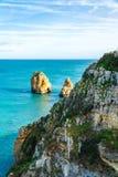 Falezy z roślinnością i skały w oceanie przy wybrzeżem Lagos, Portugalia fotografia stock