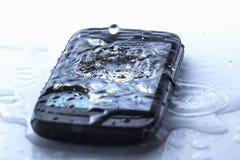 Falha esperta do telefone quebrada no assoalho de telha com água derramada Fotos de Stock