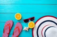 Falhanços de aleta listrados vermelhos, óculos de sol vermelhos e fruto alaranjado no fundo de madeira azul Vista superior e hora Fotografia de Stock Royalty Free