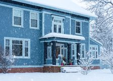Faling snow on a traditional home. Older traditional North America home in winter stock photos