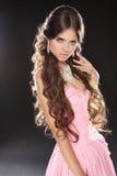 Falisty włosy. Piękna Seksowna brunetki kobieta w menchii sukni. Zdrowy Zdjęcia Stock