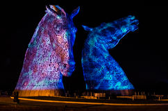 FALKIRK, SCOTLAND - APRIL 18 2014  The Kelpies are illuminated as part of the launch event. HOME  in The Helix country park in Falkirk Stock Image