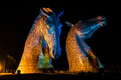 FALKIRK, SCOTLAND - APRIL 18 2014  The Kelpies are illuminated as part of the launch event. HOME  in The Helix country park in Falkirk Royalty Free Stock Photo