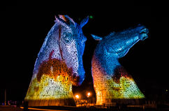 FALKIRK, SCOTLAND - APRIL 18 2014  The Kelpies are illuminated as part of the launch event. HOME  in The Helix country park in Falkirk Royalty Free Stock Photography
