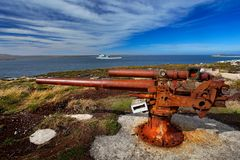 Falklands War, rocky coast with old rusty cannon. Corroded artillery gun from Falklands Conflict in nature habitat. Blue sky lands. Cape Stock Photos