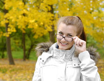 Fall. Smiling brunette teenager girl looks over glasses against fallen leaves background Royalty Free Stock Photos