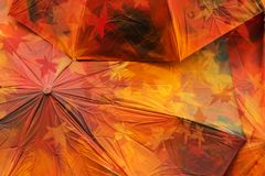 Fall abstract grunge background texture from red colored umbrellas with maple leaves. Autumn light and colors Stock Photo