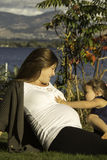 Fall is in the air. This beautiful expecting mom is enjoying the fall day with her 3 year old daughter Stock Image