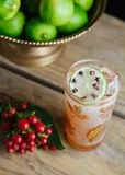 Fall alcoholic beverage in a tall pint glass. Garnished with limes on rustic background Stock Photos