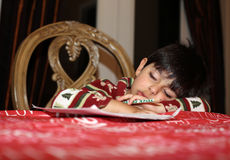 Fall asleep after studying. Young boy fell asleep while doing homework Royalty Free Stock Photography