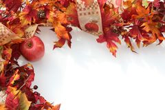 Fall or Autumn Border Horizontal. Autumn leaves, a seasonal ribbon, and a red apple compose this festive horizontal border stock photo