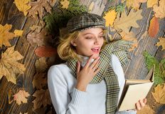 Fall and autumn season. She likes detective genre. Girl blonde lay wooden background with leaves top view. Woman lady in. Checkered hat and scarf read book royalty free stock photo