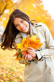 Fall / Autumn woman holding colorful leaves. In city park smiling happy. Stylish modern portrait of girl showing colorful leaves outdoor in fall forest foliage royalty free stock photo