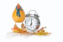 Fall Back. A front view studio shot of a silver alarm clock with a plastic rooster and fall leaves Stock Image