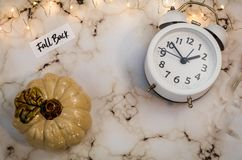 Fall Back Daylight Saving Time concept with white clock and autumn leaves stock photos