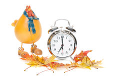 Fall Back DayLight Savings. A front close-up view studio shot of a silver alarm clock with a plastic hen and fall leaves Stock Photo